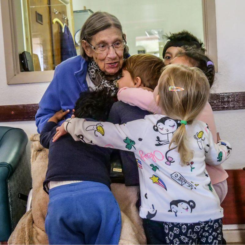 elderly woman hugging children